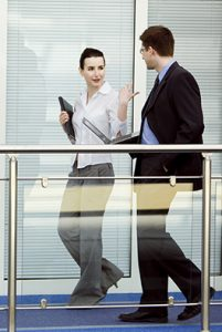 "two people walking and talking, holding web devices - image for ""Your website home page"""
