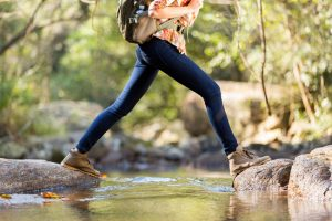 woman hiking, crossing water - Images to put in your website
