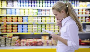 "Woman contemplating paper in store - image for ""Make decisions with emotion and logic"""