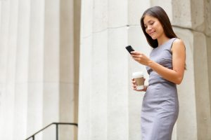 woman with coffee and cell phone