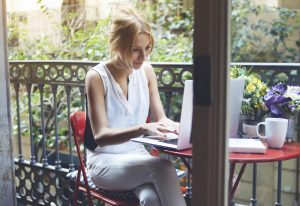 woman working on her laptop on the patio