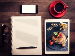 open notebook and pen, glasses, cell phone, coffee in red mug with saucer, picture of pancakes with berries